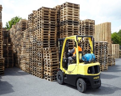 Man driving a forklift to move many objects