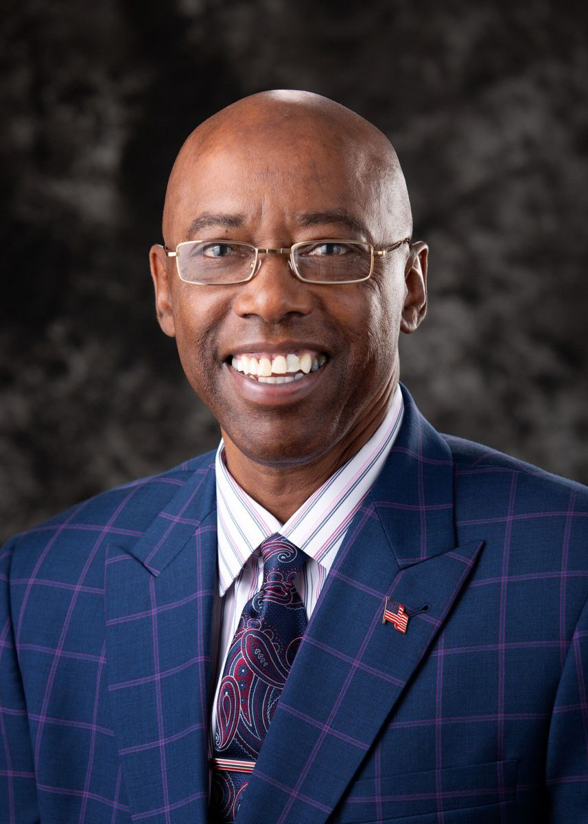 Al Steele, an African-American male, wearing gold, rectangular shaped glasses smiles while wearing a navy blue suit with white vertical and horizontal lines, a white collared shirt with gray stripes, and a tie. An American flag pin is pinned to his left jacket collar and he is pictured against a black and grey shadowed background.