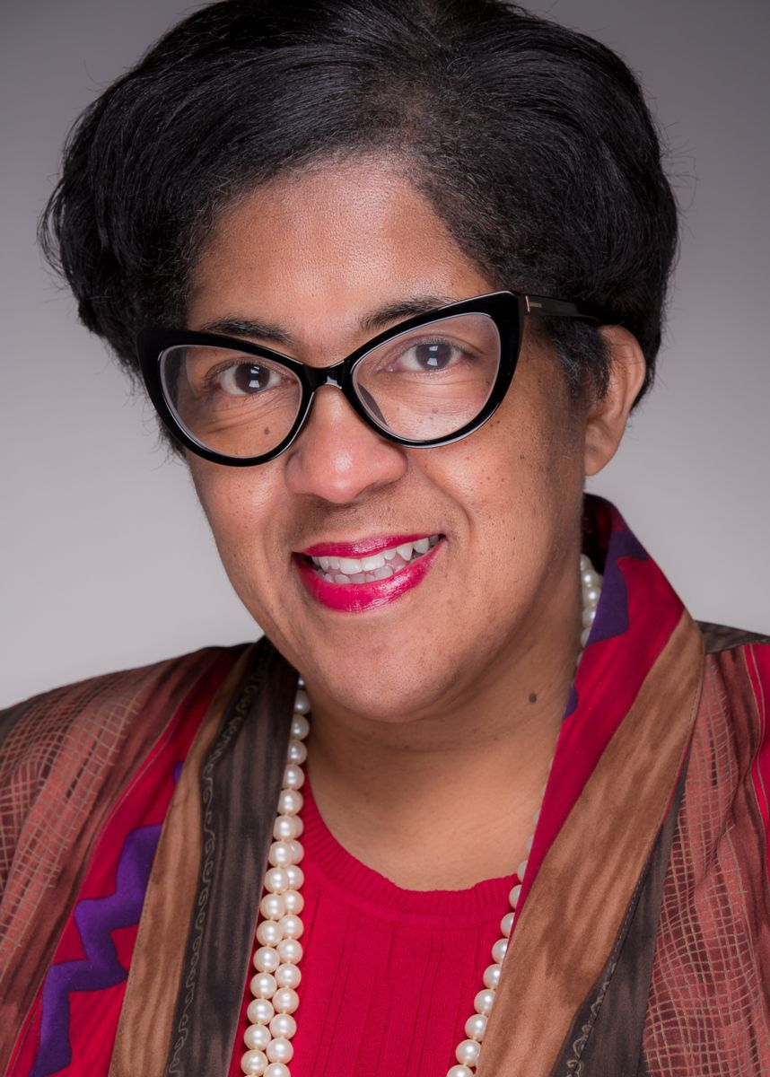 Bonita Jenkins, an African-American Female with short black hair, smiles and wears black glasses with pointed oval lenses, a 2-string pearl necklace, a suit jacket with red, brown, blue and black tones and a red shirt. She is pictured against a grey background with a gradient fading into white as it goes lower.