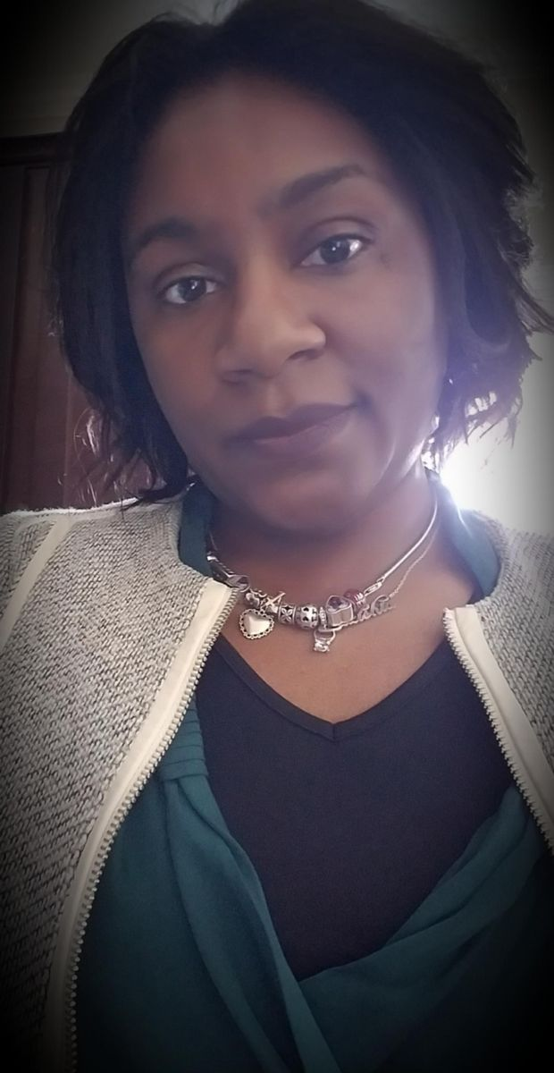 Lakishia Dinkins, an African-American female with short, wavy, dark brown hair, wears a silver charm necklace with a black, v-neck shirt under a teal v-neck over shirt, and a white and black striped jacket featuring white decorative strips.