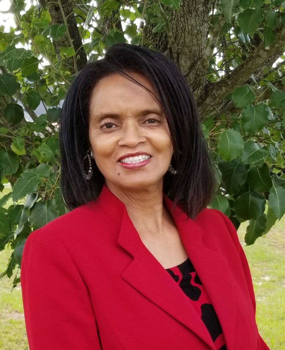 Willene Holmes, an African-American female with shoulder length black hair, stands smiling in front of a tree wearing large hoop earrings, a red suit jacket and a black and red patterned top.