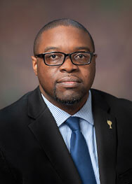 Dr. Jermain Whirl, an African American male, wears a black suit jacket with a gold pin, a blue and white striped, collared shirt; a cerulean blue tie and black square glasses. He is pictured against a foggy brown background.