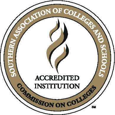 Three golden, angled, wavy lines representing a torch with the stacked words Accredited Institution in black, capitalized letters centered below it on a white circle. A golden ring lies just inside the outer edge of the circle with the words Southern Association of Colleges and Schools in white, capitalized letters on the upper 3/4s and the words Commission on Colleges in black, capitalized letters on the lower 1/4.
