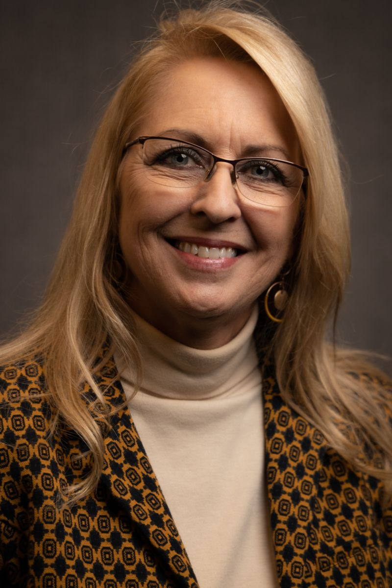 Peggy Barmore, a Caucasian female with long blonde hair wearing glasses, gold earrings, and a tan turtleneck sweater with a dress jacket with a brown diamond pattern in various shades.