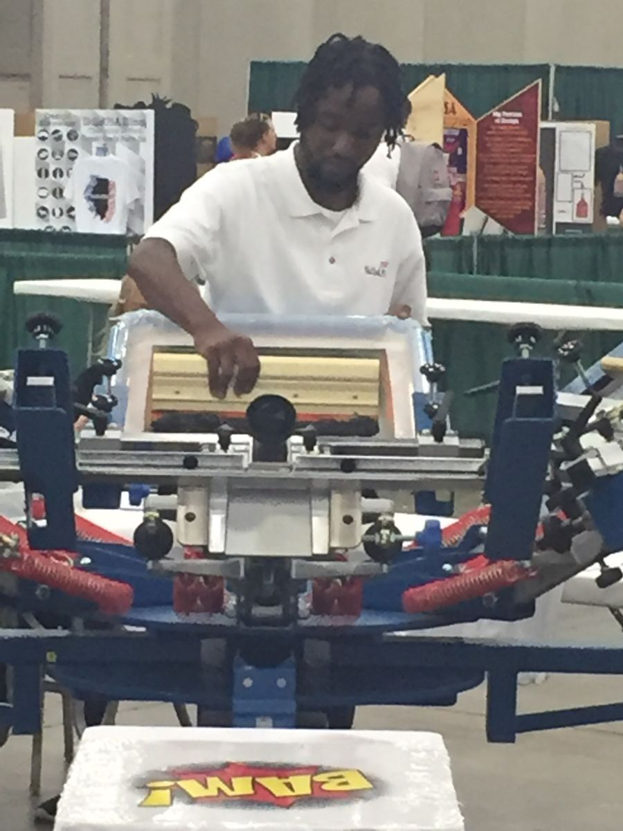 Young African American college student in white polo shirt, James McRae, works on screen printing during the competition.