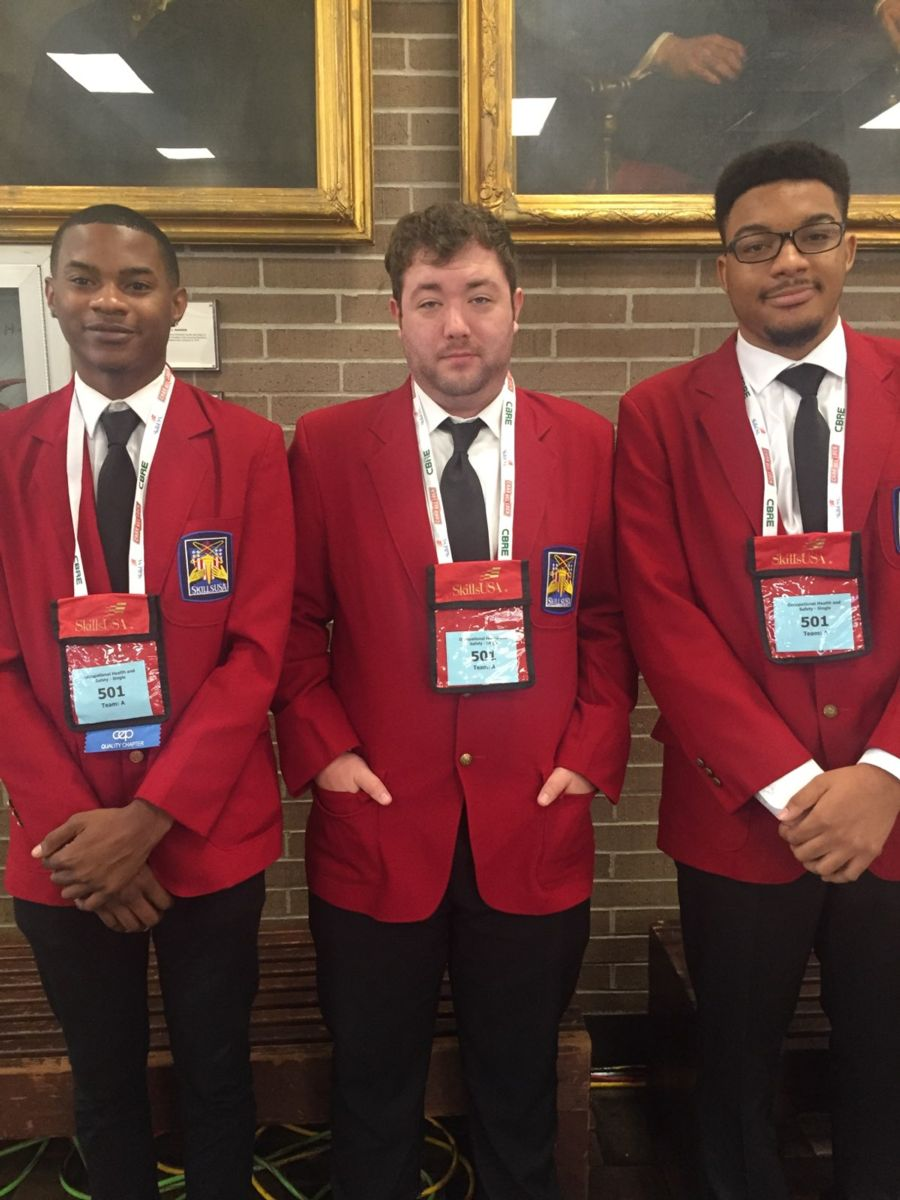 Young African American college students Joseph Currington(left), Jaeden Felder(right) and young Caucasian college student Charles Spruill(center) pose for a photo in red sports jackets and white dress shirts.