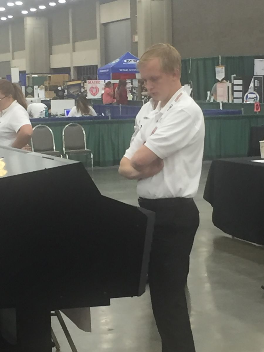 A young Caucasian college student in a white polo shirt and black dress pants, Hunter Steed, stares down at a graphics display during the competition.
