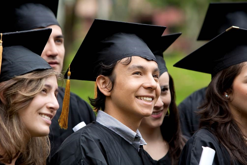 A forest green, hyperlinked, button labeled Associate Degrees in white, bolded, underlined text with an image of six graduates smile to the right of the frame in black graduate caps and gowns: A Caucasian female with sandy, brown hair stands to the right of a smiling, brown haired, Caucasian male with a blue collared shirt showing above his gown. To his left a brown haired, Caucasian female stands smiling with another brown haired, Caucasian female standing partially out of the frame to her left. A Caucasian male stands partially blocked by the first female and a sixth graduate stands hidden behind the last female.